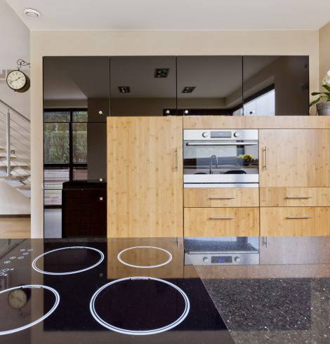 Kitchen interior with granite tabletop, wooden furniture and oven open to the staircase