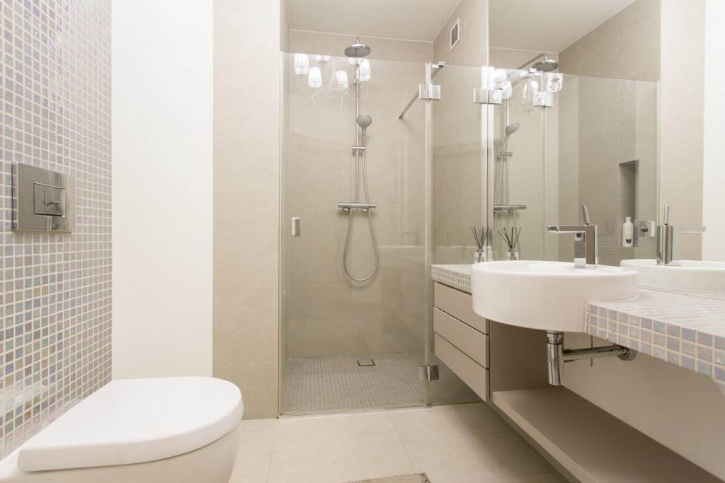 Modern, bright bathroom with glazed shower and silver decorations
